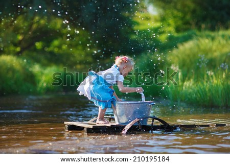 A cute little girl doing the laundry in a small aluminium basin standing on a pontoon at the pond in a sunny summer day. Kids are playing.