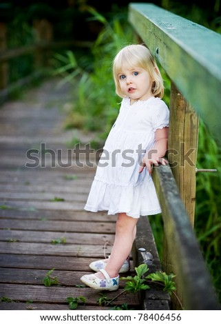 A cute little girl dressed in white leaning against the side of a boardwalk. - stock photo