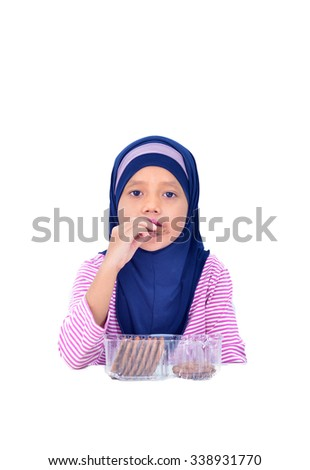 A cute little girl eating a chocolate chip cookie isolated on a white background - stock photo