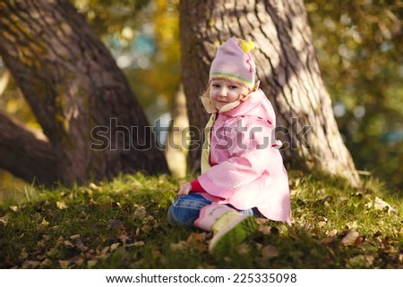 A cute little girl in a light pink coat and hat sitting on the ground in a park on a sunny autumn day