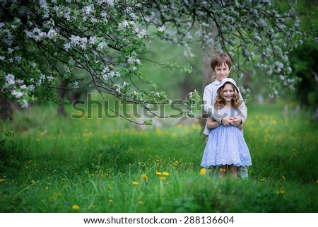 A cute little girl in an elegant white hat and light blue dress and a cute young boy embracing in the blooming garden on a sunny spring day. Kids in the country.