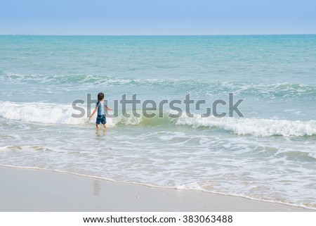 A cute little girl in playing with a toy on the beach on a warm sunny summer day. Holidays at sea. Funny kids