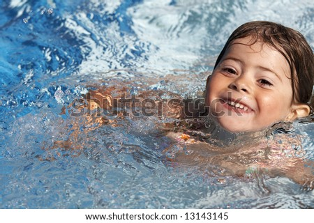 a cute little girl in pool water during the summer - stock photo