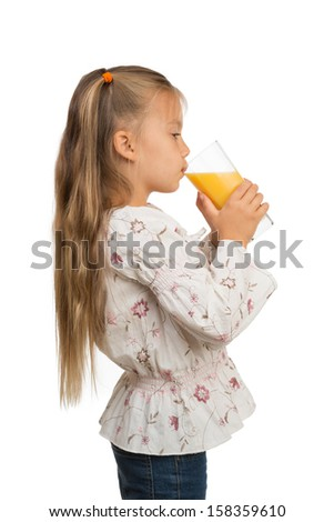 A cute little girl is holding a glass with orange juice with both hands, drinking from it - stock photo