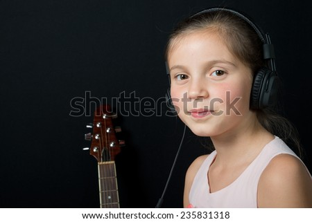 a cute little girl listening to music with black headphones - stock photo