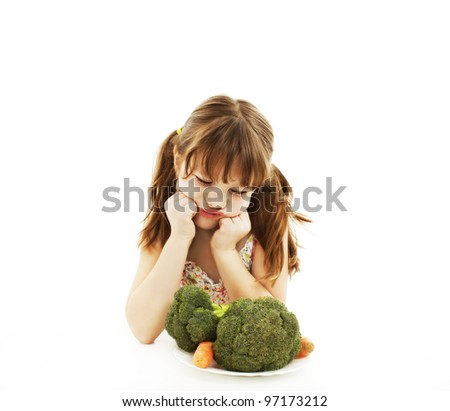 A cute little girl looks in disgust at her plate of vegetables. Isolated on White Background. - stock photo