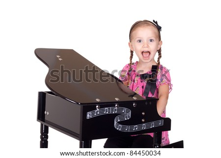 A cute little girl plays with her piano.