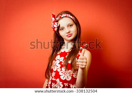 A cute little girl showing thumbs up - stock photo