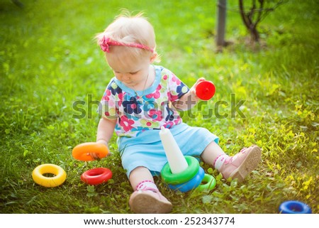 A cute little smiling girl playing in the meadow in a sunny summer day - stock photo