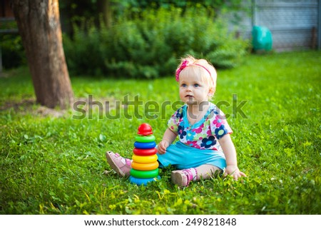 A cute little smiling girl playing with clover flowers in the meadow in a sunny summer day - stock photo