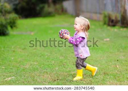A cute little toddler girl holding a pet toy- a colorful rope ball in the park on a cool summer or autumn day - stock photo