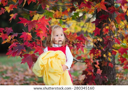 A cute little toddler girl holding a warm cozy blanket standing under a colorful autumn tree