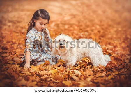 A cute little toddler with  her dog, a yellow in a park with autumn trees in the background