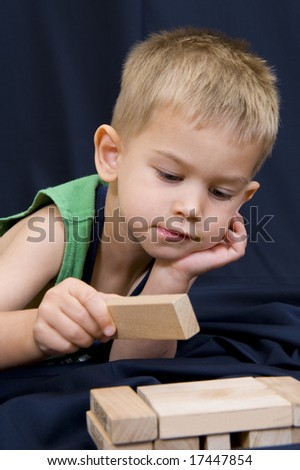 A cute little 3 year old boy playing on a black background with some wooden blocks.