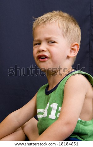 A cute little 3 year old boy with a sad or angry face.