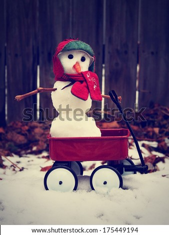 a cute miniature snowman in a red wagon done with a retro vintage instagram filter - stock photo