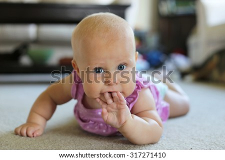 A cute 6 month old baby girl is laying on her tummy at home sucking on her fingers. - stock photo
