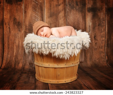 A cute newborn baby is sleeping in a wooden basket with a wooden background and is wearing a hat for a photography portrait or love concept.