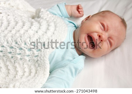 A cute one month old newborn baby is laying on her back in the crib, crying. - stock photo
