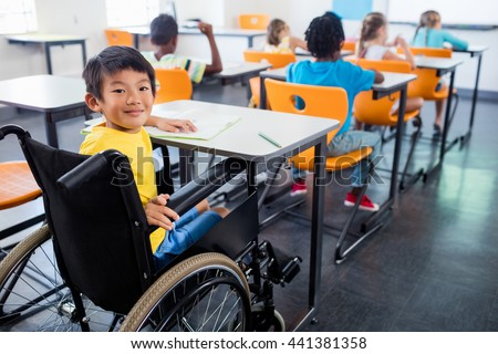 A cute people in wheel chair looking at the camera in classroom - stock photo