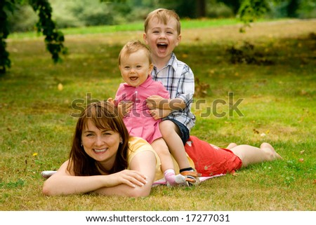 A cute portrait of a mother lying on the lawn with her children sitting on her back, in the outdoors.