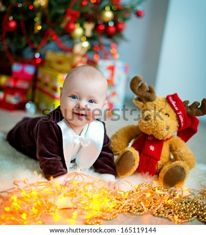A cute round-faced little boy in an elegant tail-coat lying against the Christmas Tree with a toy and smiling - stock photo