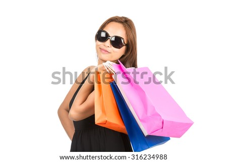 A cute sassy Asian girl with sunglasses smiles, carrying colorful department store shopping bags flung over shoulder facing camera. Half length isolated on white. Thai national of Chinese origin - stock photo