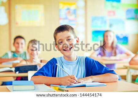 A cute schoolboy sitting in his classroom with his classmates. - stock photo