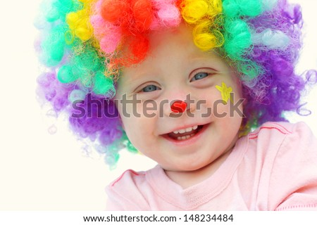 A cute, smiling baby boy is dressed up in a clown costume with colorful wig and clown make up face paint - stock photo