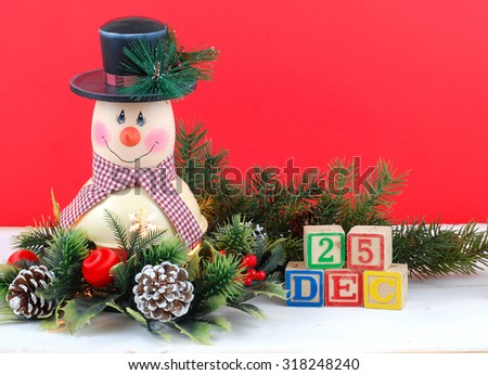 A cute snowman decoration with lamp inside is surrounded by holly, pine, pine cones and Christmas decorations. Bright red background. Dec 25th in letter block with copy space upper right. - stock photo
