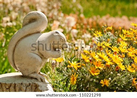 A Cute Stone Chipmunk Statue Made of Stone in a Yard Setting With Flowers - stock photo