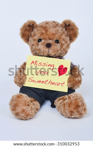 A cute teddy bear holding a yellow sign that says Missing my sweetheart isolated on a white background