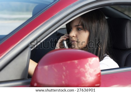 a cute teen driving on cell phone - stock photo