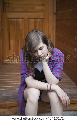 A cute teenage girl sitting on the bleacher steps with a serious expression - stock photo