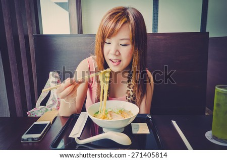 A cute Thai girl is eating a Japanese Ramen in the resturant in vintage color. This is urban life. - stock photo