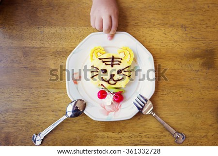 A cute tiger decorated cake with a kid's hand background.