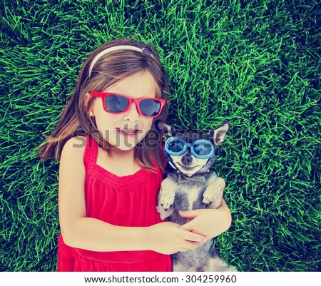 a cute toddler girl with red sunglasses on holding a chihuahua with goggles on in the grass in a park or backyard with a green lawn toned with a retro vintage instagram filter effect app or action