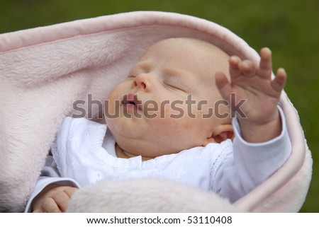 a cute 7 weeks old baby girl reaching out her hand to her mother´s breast while sleeping