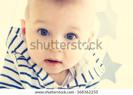 A cute white baby boy with big blue eyes is looking surprisingly into the camera and wearing striped hooded sweater. Light background with two grey stars. Parenting or love concept - stock photo