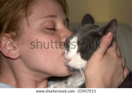 A cute woman kissing a cat - stock photo