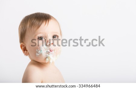 a cute 1 year old sits in a white studio setting. Close up of a baby with a face full of cake and frosting. He is only dressed in a white diaper - stock photo