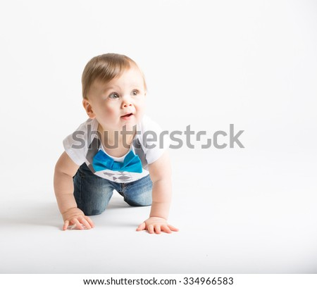 a cute 1 year old sits in a white studio setting. The boy is crawling and looking up right off camera with surprised look. He is dressed in Tshirt, jeans, suspenders and blue bow tie
