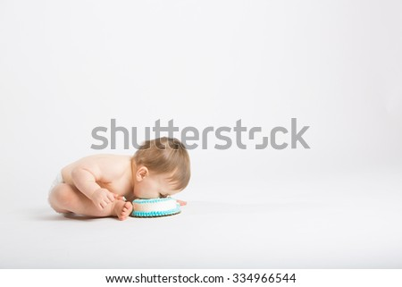 a cute 1 year old sits in a white studio setting. The boy is eating a face full of cake by leaning over into it.copyspace on the right. He is only dressed in a white diaper - stock photo