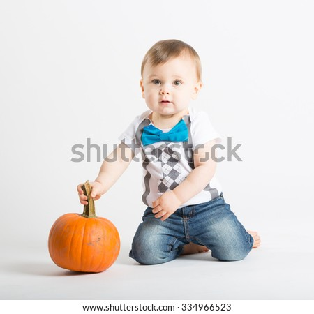 a cute 1 year old sits in a white studio setting with a pumpkin. The boy looks up holding pumpkin stem while kneeling. He is dressed in t-shirt, jeans, suspenders and blue bow tie
