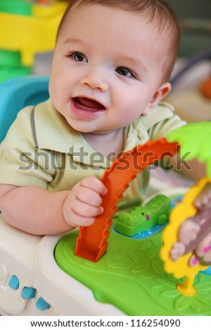 A cute young baby boy playing with his toys - stock photo