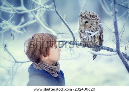 A cute young boy in a warm knitted clothes looking at the owl sitting on the branch covered with frost on a frosty winter day. Kids and nature. - stock photo