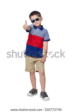 A cute young boy in the shirt with his thumb up stands against the white background. - stock photo
