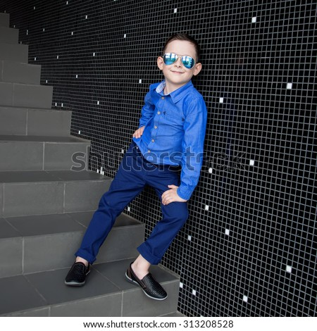 A cute young boy is dressed in a blue shirt and trousers. He wears sunglasses.Studio shot - stock photo