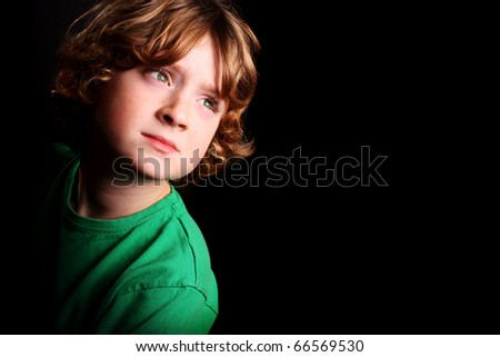 A cute young boy looking upwards on a black background.