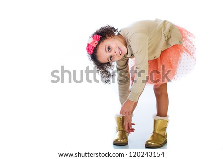 A cute young child putting her gold boots on. - stock photo